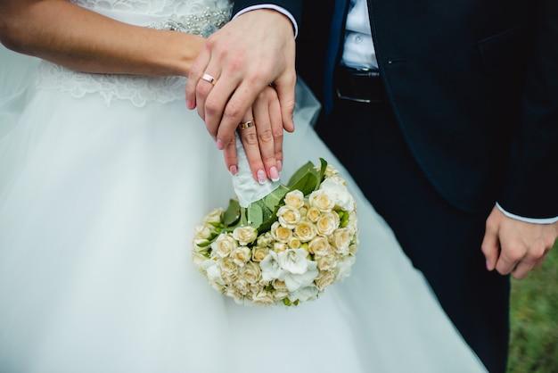 Closeup nouveaux mariés montrent leurs alliances