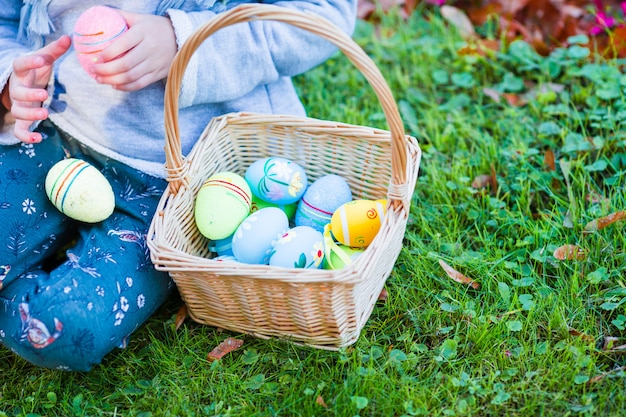 Closeup panier plein d'oeufs de pâques colorés dans les mains des enfants