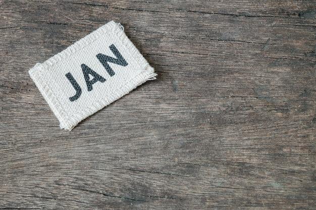 Closeup petit picec de calendrier en tissu au mois de janvier sur fond de bureau en bois