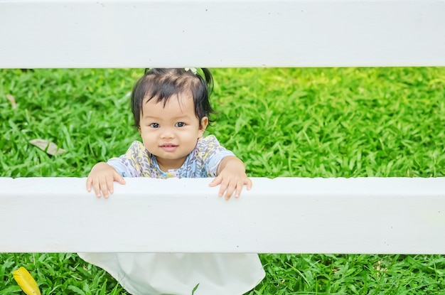 Closeup, petite fille, attraper, a, clôture blanche, sur, herbe, fond, jardin, sourire