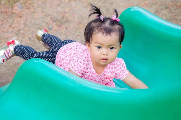 Closeup petite fille a menti sur le curseur vert au fond de l'aire de jeu