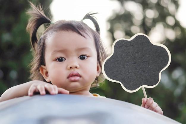 Closeup petite fille avec un tableau noir en bois dans le fond de la vue de jardin