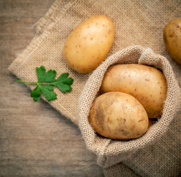 Closeup pommes de terre biologiques fraîches sur fond de sac de chanvre.