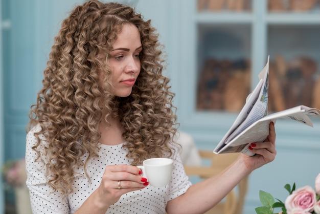 Closeup portrair de jolie fille lisant un journal et tenant la tasse de thé. - image