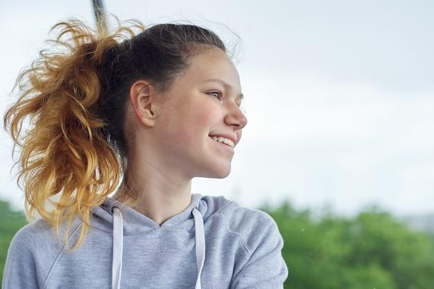 Closeup portrait d'adolescente de 14, 15 ans en sweat gris