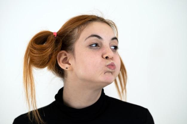 Closeup portrait d'une adolescente rousse drôle avec une coiffure enfantine isolée