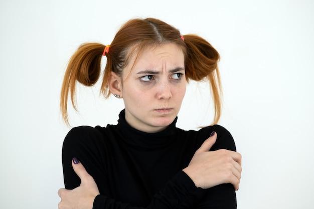 Closeup portrait d'une adolescente rousse triste avec une coiffure enfantine à l'isolement offensé