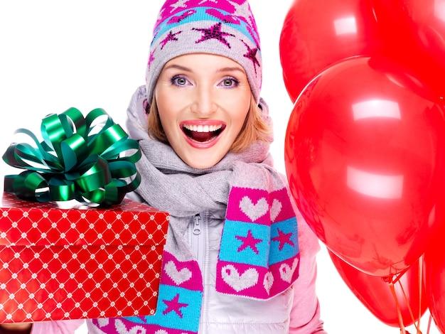 Closeup portrait de l'amusement femme adulte heureuse avec boîte-cadeau rouge et ballons isolés sur blanc
