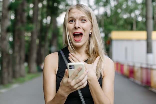 Closeup portrait anxieux jeune fille regardant téléphone voir de mauvaises nouvelles ou des photos avec une émotion dégoûtante sur son visage isolé à l'extérieur du fond de la ville. émotion humaine, réaction, expression