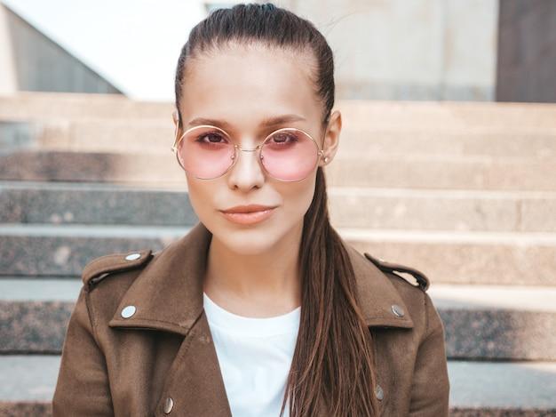 Closeup portrait de beau modèle brune vêtue d'une veste hipster d'été. fille branchée, assis sur les marches dans le fond de la rue. femme drôle et positive en lunettes de soleil rondes