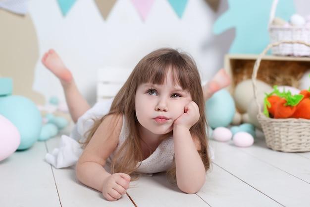 Closeup portrait d'un beau petit visage de fille. beaucoup d'oeufs de pâques colorés, décoration intérieure de pâques colorée. lapin de pâques, carotte et drapeaux colorés. l'enfant ressent du ressentiment et fronce les sourcils. émotions de l'enfant.