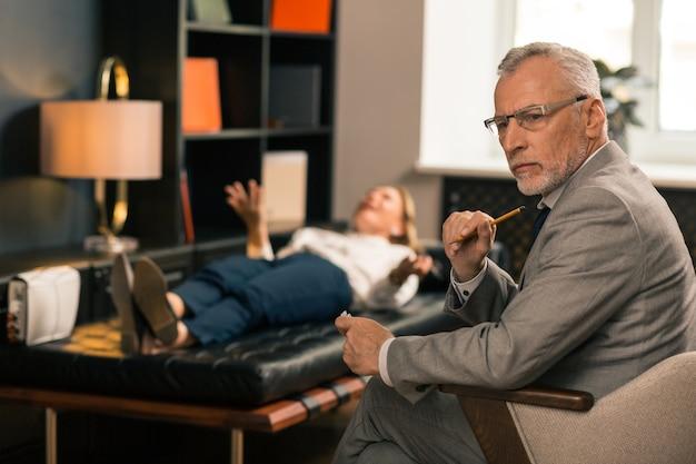Closeup portrait d'un beau psychiatre aux cheveux gris sérieux assis dans son bureau tout en pensant et en détournant les yeux