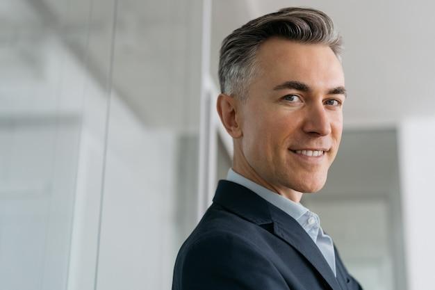 Closeup portrait de bel homme d'affaires mature regardant la caméra au bureau. entreprise prospère