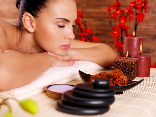 Closeup portrait d'une belle femme adulte se détendre dans le salon spa.