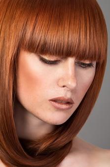 Closeup portrait de belle femme aux cheveux rouges