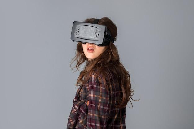 Closeup portrait de belle femme en casque de réalité virtuelle en studio sur mur gris