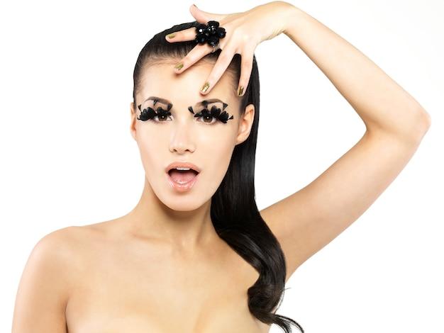 Closeup portrait de la belle femme avec de longs faux cils noirs maquillage et ongles dorés. isolé sur un mur blanc