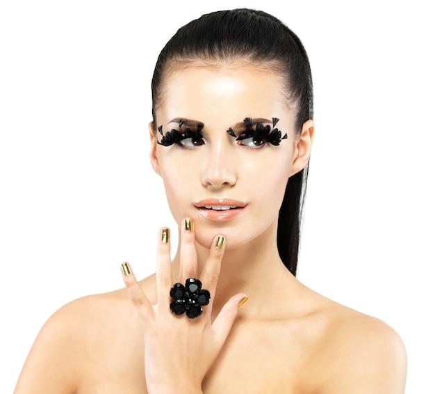 Closeup portrait de la belle femme avec de longs faux cils noirs maquillage et ongles dorés.
