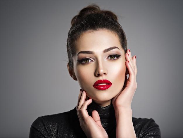 Closeup portrait de belle femme avec maquillage lumineux et ongles rouges. sexy jeune fille adulte avec rouge à lèvres.