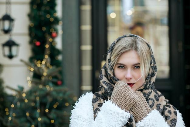 Closeup portrait de belle femme porte manteau et écharpe en tricot posant à la ville. espace pour le texte