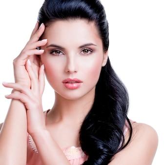 Closeup portrait de la belle femme sensuelle aux longs cheveux brune - isolé sur un mur blanc.