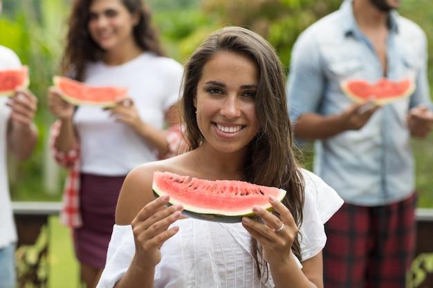 Closeup portrait de belle femme tenant la pastèque avec des amis heureux joyeux groupe de personnes h