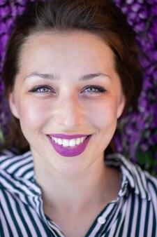 Closeup portrait de belle fille souriante allongée sur un tapis de fleurs de lupin