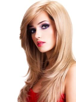 Closeup portrait d'une belle jeune femme aux longs cheveux blancs. mannequin posant sur un mur blanc
