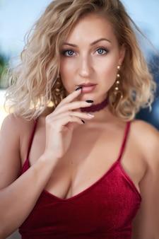 Closeup portrait d'une belle jeune femme blonde en regardant la caméra.