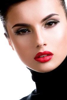 Closeup portrait d'une belle jeune femme avec du maquillage de mode posant isolé sur blanc.