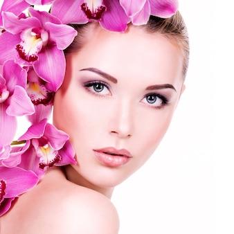 Closeup portrait de belle jeune femme avec une peau propre et saine du visage. jolie fille adulte avec une fleur près du visage. - isolé sur fond blanc