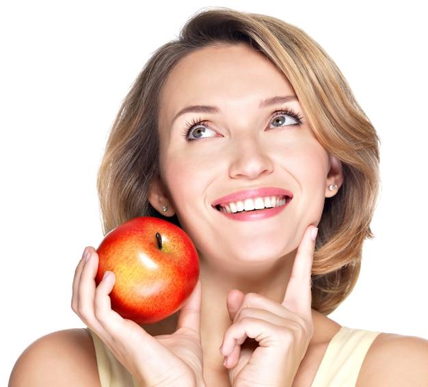 Closeup portrait d'une belle jeune femme souriante pointant le doigt pointé vers le haut isolé sur blanc.