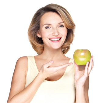 Closeup portrait d'une belle jeune femme souriante pointant vers apple - isolé sur blanc.