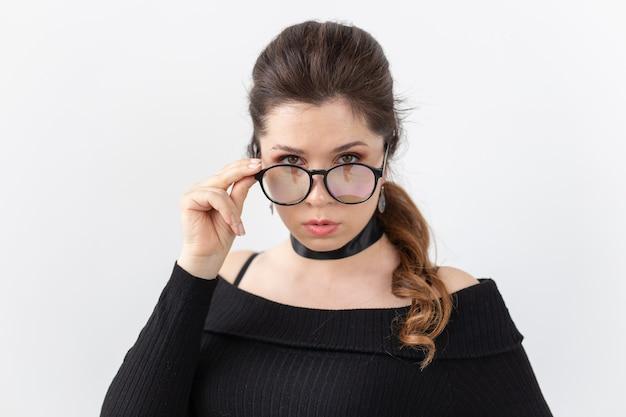 Closeup portrait d'une belle jeune femme en vêtements noirs avec un ruban sur son cou tenant des lunettes posant sur un mur blanc. concept d'une jeune étudiante ou femme d'affaires intelligente