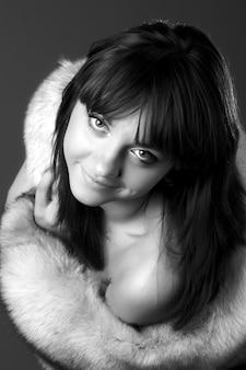 Closeup portrait d'une charmante jeune fille aimable posant avec fourrure grise posant
