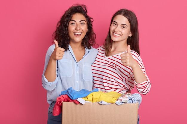 Closeup portrait de deux femmes souriantes montrant les pouces vers le haut et posant isolé sur fond de studio rose