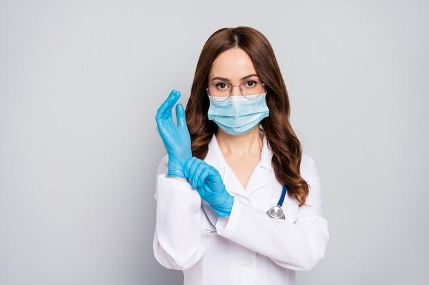 Closeup portrait d'elle elle belle attrayante et confiant doc chirurgien aux cheveux ondulés phonendoscope stéthoscope mettant des gants sur la préparation du service de chirurgie isolé sur fond de couleur pastel gris