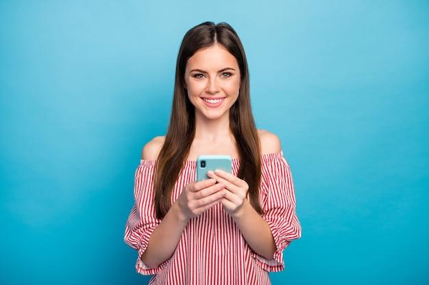 Closeup portrait d'elle elle belle jolie fille aux cheveux bruns joyeux joyeux à l'aide de gadget appareil numérique à la recherche de médias isolés sur fond de couleur bleu vif brillant éclatant