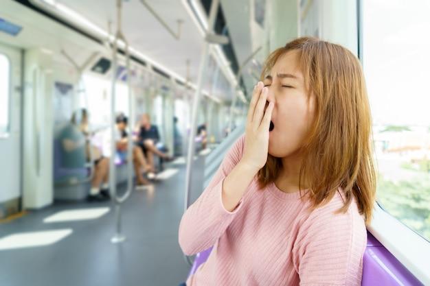 Closeup portrait endormi, bailler, fermer les yeux jeune femme dans le train du ciel après un voyage de longue heure.