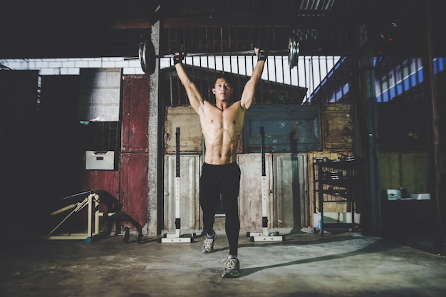Closeup portrait d'un entraînement musculaire homme avec haltères au gymnase local