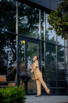 Closeup portrait d'une femme d'affaires debout à l'extérieur de l'immeuble de bureaux et parlant au téléphone portable