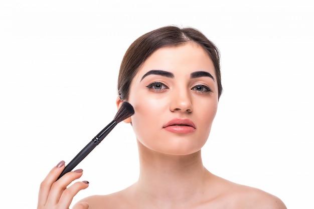 Closeup portrait d'une femme appliquant un fond de teint cosmétique sec sur le visage à l'aide d'un pinceau de maquillage.