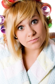 Closeup portrait de femme au foyer drôle avec bigoudis sur blanc