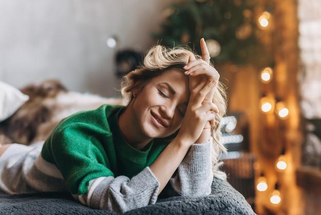 Closeup portrait d'une femme charmante blonde aux yeux fermés dans un pull vert se trouvant sur un canapé