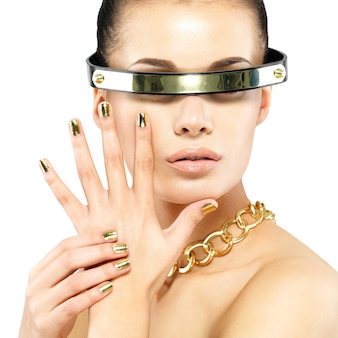 Closeup portrait de femme avec des clous dorés et chaîne en or sur le cou