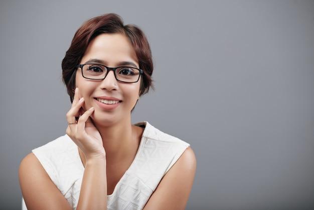 Closeup portrait de femme indienne souriante regardant la caméra sur fond gris