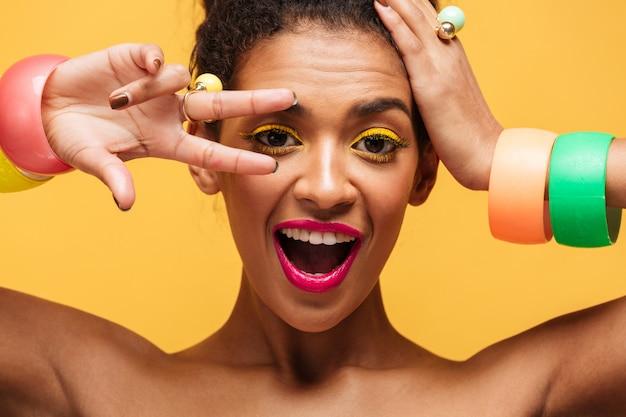 Closeup portrait de femme mulâtre ludique avec des paupières jaunes et des lèvres roses gesticulant deux doigts à l'oeil et regardant la caméra, isolé