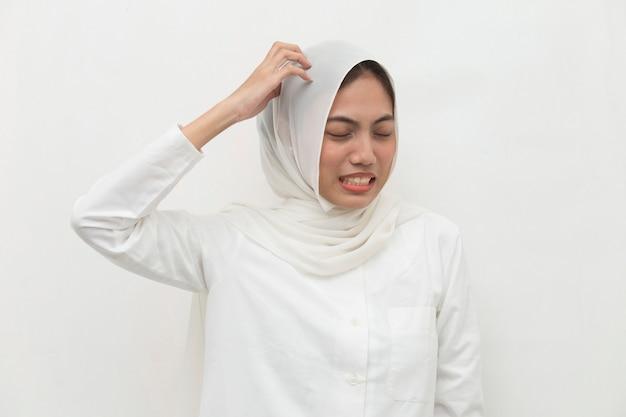 Closeup portrait de femme musulmane asiatique se gratter la tête avec la main