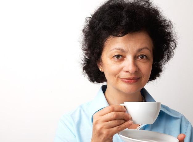 Closeup portrait d'une femme souriante aînée tenant la tasse et la soucoupe.