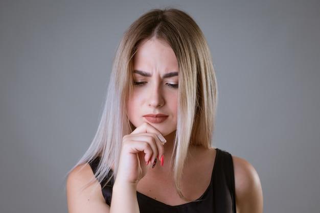 Closeup portrait d'une femme avec un visage froncé sur un mur de lumière femme blonde en tshirt noir